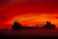 A Lake Superior freighter is silhouetted at dawn with the upper harbor breakwater light in Marquette, Mich.