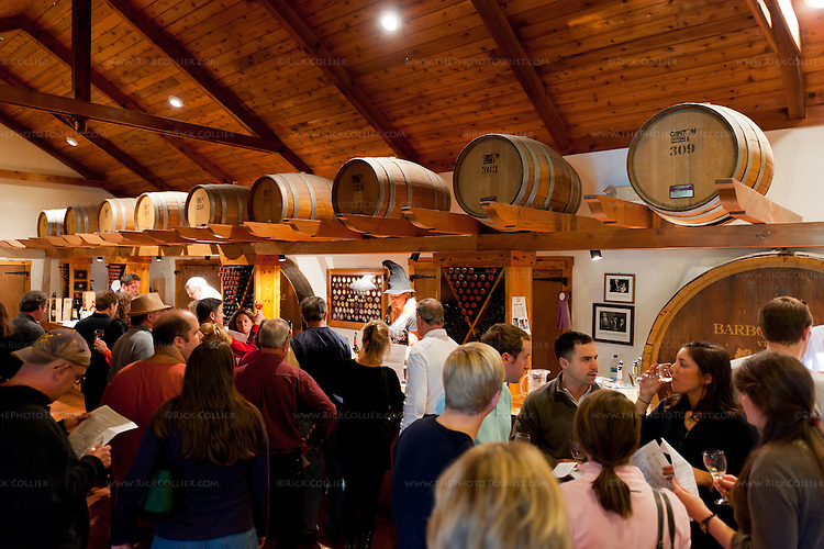 On a busy day visitors throng the tasting room at Barboursville Vineyards.  Visitors here move through the tasting room from window to window.  Each window pours samples of different wines.