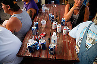 Empy beer cans and cigarette packs lay on a picnic table during the Testicle Festival at the Rock Creek Lodge in Clinton, MT.  The Rock Creek Lodge in Clinton, MT, has hosted the annual Testicle Festival since the early 1980s.  The four day festival and party revolves around the consumption of so-called Rocky Mountain Oysters, which are deep-fried bull testicles.