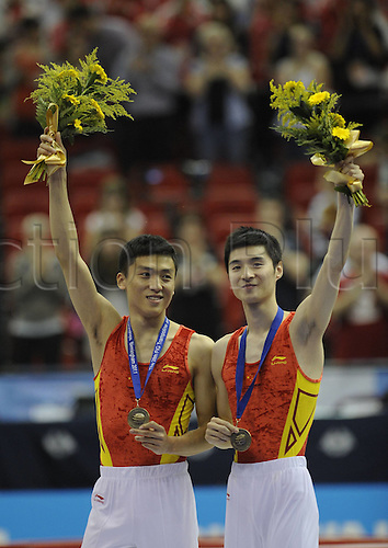 20.11.2011. Birmingham England. Gold Medalists Dong Dong and Tu Xiao of China Pose on The Podium After the mens trampoline Synchronized Final of The 2011 trampoline and Tumbling World Championships in Birmingham Britain. Dong and Tu of China Won by 52,400 Points with Japans Sakamoto Takashi Ueyama Yasuhiro and Belarus'  Modzel Mikalai Kazak Ranking Second and Third