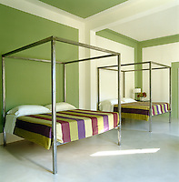 Painted panels in alternating pea-green and white are a stunning yet simple visual device when juxtaposed against the shape of the four-poster beds in this contemporary guest bedroom