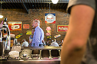 Vice President Joe Biden poses for a picture during an unscheduled stop at Smokey Row Coffee during a two-day campaign swing through Iowa on Tuesday, September 18, 2012 in Oskaloosa, IA.