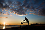 A woman stretches against a bench on a hill overlooking a bay at sunset.