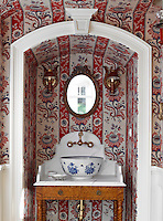 A blue and white porcelain wash basin on a stand is situated in an alcove lined in a floral red and white striped wallpaper