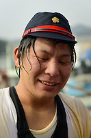 """Drenched and cold participant. Housui Gassen (fire-hose battle), Bizen city, Okayama pref, Japan, February 2, 2014. The annual Bizen """"Housui Gassen"""" (fire-hose battle) takes place in the Hinase port area. Opposing teams of fire-fighters spray each other with hoses before the event culminates with a display of coloured water from the hoses."""