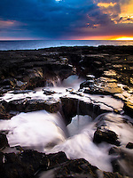 At sunset, waves surge and recede through openings along Keahole Point's rocky shoreline on the Big Island.