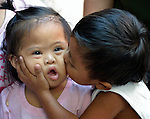 In Abucay, a seaside town in the Philippines province of Bataan, a girl with Down Syndrome gets a kiss from her brother.