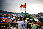 Two boys take in the view of the neighborhood that surrounds the 2,600-ton ship which landed 2-miles inland when the tsunami receded back to the bay, in Banda Aceh, Indonesia, Sunday, Nov. 8, 2009. On Dec. 26, 2004, a 9.0 magnitude earthquake triggered a massive tsunami that killed 226,000 people throughout several countries. In Aceh, the death toll alone was 166,000.