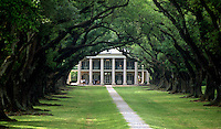 Exterior view of Oak Alley plantation house framed at the end of a tree-lined boulevard. Vacherie, Louisiana.