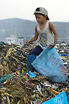 Children working in the municipal dump in Manila, the capital of the Philippines. Children and their parents work day and night in the dump, scavenging for items of value, including plastic, glass and metal, that can be recycled.