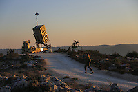 """Israeli soldier walks near an """"Iron Dome"""" battery, a short-range missile defence system, designed to intercept and destroy incoming short-range rockets and artillery shells, near Jerusalem on September 9, 2013 as the United States lobbied for domestic and international support for military strikes against Syria. Photo by Oren Nahshon"""