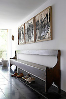 An antique church bench in the hallway sits under a multi-media triptych by the American artist Koschmider