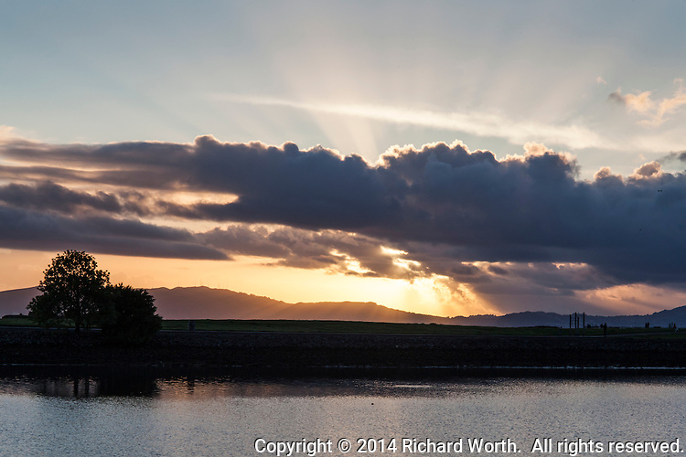Near sunset, the golden glowing sun peeks through clouds hovering over the par course at San Leandro Marina Park on the San Francisco Bay.