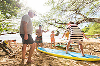 A family takes a surfing lesson at a beach at Pua'ena Point, North Shore, O'ahu.
