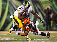 Fitzgerald Toussaint #33 of the Pittsburgh Steelers is tackled while carrying the ball by Derron Smith #40 of the Cincinnati Bengals during the Wild Card playoff game at Paul Brown Stadium on January 9, 2016 in Cincinnati, Ohio. (Photo by Jared Wickerham/DKPittsburghSports)