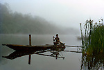 Early morning on the Bensbach River, Western Province, Papua New Guinea.    //  A villager from nearby Balumuk Research Station (now derelict) readies his canoe for a dawn patrol of the Bensbach River. He is checking nets set overnight for catfish and barramundi that breed in the river. The mouth of the Bensbach River marks the southern boundary between Papua New Guinea and Irian Jaya. Adjacent to the canoe mooring is the wide Bula Plains area, sparsely treed and seasonally flooded during the wet season Dec - March, and totally dry during the dry season in the middle of the year. A large population of Javan Rusa Deer (Cervidae: Rusa timoriensis), a tropical deer introduced from south-east Asia early in the 20th Century to southern-central New Guinea, inhabit this open plain. IUCN Status: Vulnerable.  // Dr Eric Lindgren, EL, PS. //