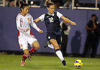 BOCA RATON, FL - DECEMBER 15, 2012: Lauren Cheney (12) of the USA WNT takes a shot past Wang Dongni (14) of China WNT during an international friendly match at FAU Stadium, in Boca Raton, Florida, on Saturday, December 15, 2012. USA won 4-1.