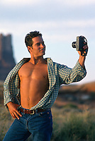 Man with an open shirt taking a photograph of himself out in the desert