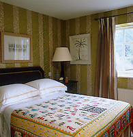 The guest bedroom has a colourful applique bedcover and striped wallpaper with a botanical print