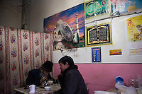 Uighur men eat in a small restaurant in the Old City section of Kashgar, Xinjiang, China.