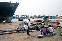 Fishemen chat at a boat reparing workshop at Cuddalore which was destroyed in 2004 Tsunami. Tamil Nadu, India.