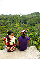 Two young women enjoying the view from the top of Temple IV, Maya ruins of Tikal, El Peten, Guatemala. Tikal is a UNESCO World Heritage Site....