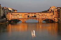 General view of the Ponte Vecchio, Florence, Tuscany, Italy, pictured on June 8, 2007, in the evening. The Ponte Vecchio, or Old Bridge, crosses the River Arno at its narrowest point. The original bridge, possibly Roman and first documented in 999, was swept away in a flood in 1117, rebuilt, swept away again in 1333 and rebuilt in 1345. In 1565 Cosimo de Medici commissioned Vasari to design a corridor, above the famous shops along the bridge, connecting the Palazzo Vecchio to the Pitti Palace. In 1593 the Medicis prohibited butchers, the traditional occupants, from the shops which were soon taken by Goldsmiths. Florence, capital of Tuscany, is world famous for its Renaissance art and architecture. Its historical centre was declared a UNESCO World Heritage Site in 1982. Picture by Manuel Cohen.