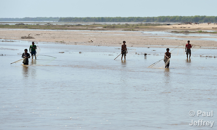 Wichi indigenous men fishing in the Pilcomayo River in Santa Victoria Este, Argentina. The Wichi in this area, largely traditional hunters and gatherers, have struggled for decades to recover land that has been systematically stolen from them by cattleraisers and large agricultural plantations, and to preserve their access to a river which has suffered increasing levels of contamination from upstream mining and other uses. After years of negotiation supported by Church World Service, a landmark 2014 agreement will divide the land in this region between indigenous communities and settlers, guaranteeing the survival of the Wichi and their access to the river.