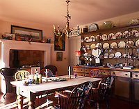 A large dresser filled with plates dominates this kitchen and Windsor chairs surround the scrubbed table next to the range
