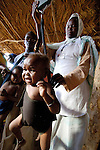 A baby is weighed in a health center in the Hassahissa IDP Camp near Zalingei where displaced children's growth is closely monitored and their families provided with supplemental food. The center is sponsored by ACT-Caritas.