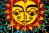 Close-up of a beautiful tile  panel depicting a colorful sun in Einsiedeln, Switzerland.
