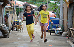 Necabless Barrio (right), is a 12-year old girl on Bayas, a small island in the Philippines municipality of Estancia, in Iloilo Province. Here she runs with her friend Francenn Sulayao.<br /> <br /> The island was ravaged by the passage of Typhoon Haiyan, known locally as Yolanda, in November 2013. Both deaf and mute, Barrio fled with her family as the waters rose, but got her foot tangled in some electrical cables. With the water at the girl's neck and still rising, her mother managed to free her and get her to higher ground.