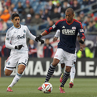 New England Revolution forward Teal Bunbury (10) dribbles as Vancouver Whitecaps FC midfielder Matias Laba (15) closes. In a Major League Soccer (MLS) match, the New England Revolution (blue/white) tied Vancouver Whitecaps FC (white), 0-0, at Gillette Stadium on March 22, 2014.