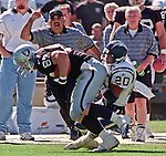 Oakland Raiders vs. San Diego Chargers at Oakland Alameda County Coliseum Sunday, September 3, 2000.  Raiders beat Chargers  9-6.  San Diego Chargers defensive back Mike Dumas (20) hangs on to Oakland Raiders tight end Jeremy Brigham (87).
