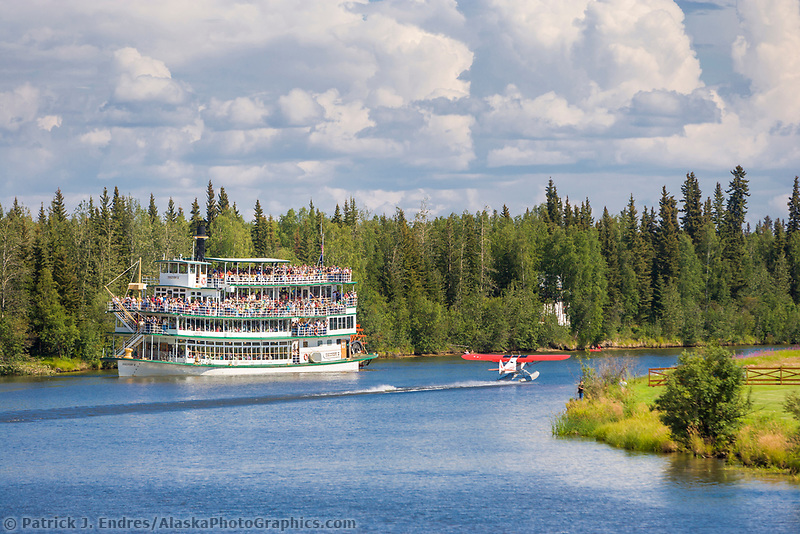 Riverboat Discovery sternwheeler with tourists, bush plane on floats takes off from the Chena River, Fairbanks, Alaska.