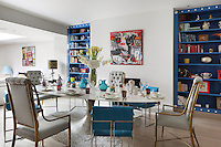 A spacious open plan dining room has an unexpected combination of seating around a steel table - short turquoise leather chairs on architectural Milo Baughman chrome frames and the taller sloping shapes of the brass framed, button backed chairs with pale silvered fabric