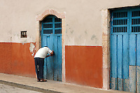 Man bending over to lock an old wooden door in Santa Elena, Yucatan, Mexico.