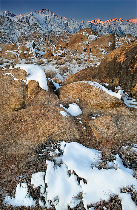 711700283 winter sunrise with snow covered granite boulders in the bureau of land management protected land the alabama hills in the southern section of the eastern sierras with lone pine peak mount whitney and mount russell in the background in kern county california