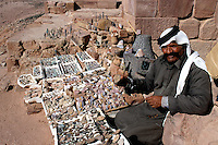 "Jordan. Petra. The archeological site is part of the UNESCO world heritage project.  The Nabataeans were an arabian industrious tribe which settled down in southern Jordan 2000 years ago. Petra is located at the bottom of a spectacular deep gorge surrounded by mountains. ""Urnel Florentius"" tomb. A bedouin man wears a long dress and a turban as part of muslim tradition and religion. His business is to sell ethnic antique stones, coins and potteries to tourists.  © 2002 Didier Ruef"