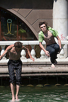 Moscow, Russia, 25/06/2010..Two young men jump down from a shopping centre balcony into fountains next to the Kremlin and Red Square during a heatwave that has seen temperatures of up to 37C, a record for the month of June.