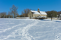 Quaint 13th Century chapel in snow-covered Windrush valley at Widford, The Cotswolds, UK