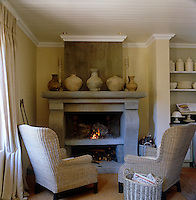 A pair of wicker armchairs creates an intimate sitting area around the fireplace in a corner of the galley kitchen