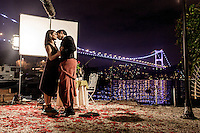 Actors kiss, on a set during filming of a televison show, on the Anatolyan/Asian shore of the Bosphorus with the Bosphorus Bridge illuminated in the background.