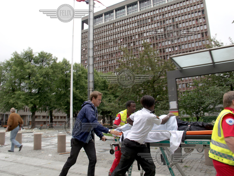 Oslo Norway 20110722 -  Terror attack on the government quarters in Oslo and AUF youth camp at Utoya / Ut&oslash;ya.  Pictured: injured person taklen away by paramedics in front of the the government building, housing among others the prime minister&acute;s office (Regjeringsblokka), 18 minutes after the attack. Photo/copyright: Torbjorn Gronning.