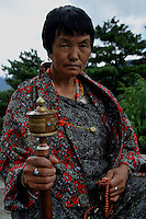 A bhutanese lady with a prayer wheel in her hand. Thimpu. Bhutan. Arindam Mukherjee..