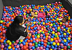 Mimi Ocampo takes a picture of her younger daughter, Meli, in a ball pit at a birthday party for a friend's daughter in London, Ky., on Thursday, Oct. 25, 2012. Ocampo took Meli and her other daughter, Naomi, to the party. Her son, Ozzi, spent the night with his dad, whom Ocampo is separated from.   Photo by Taylor Moak