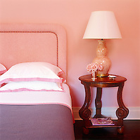 In an East Hampton bedroom dominated by tones of coral-pink, rose and violet a pleasing note of contrast is created by a Chinese rosewood bedside table