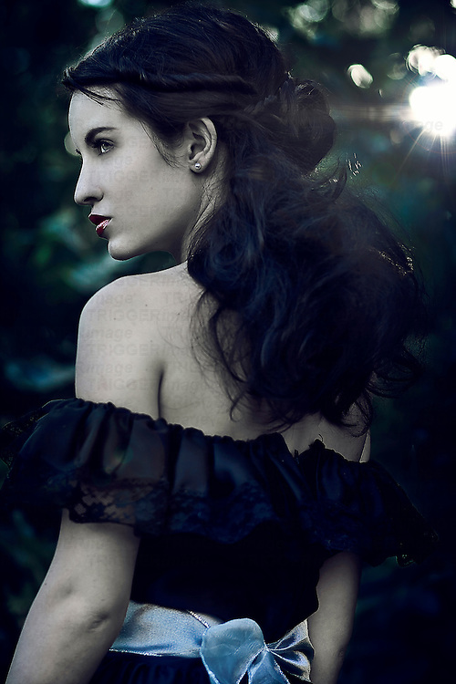 A girl wearing a black dress, surrounded by foliage.