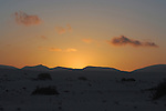 Low hills in the background as the sun sets over sand dunes, Corralejo, Fuerteventura, Canary Islands, Spain.