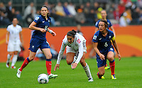 Carli Lloyd (C) of team USA and Sandrine Soubeyrand (r) and Elise Bussaglia of team France during the FIFA Women's World Cup at the FIFA Stadium in Moenchengladbach, Germany on July 13th, 2011.